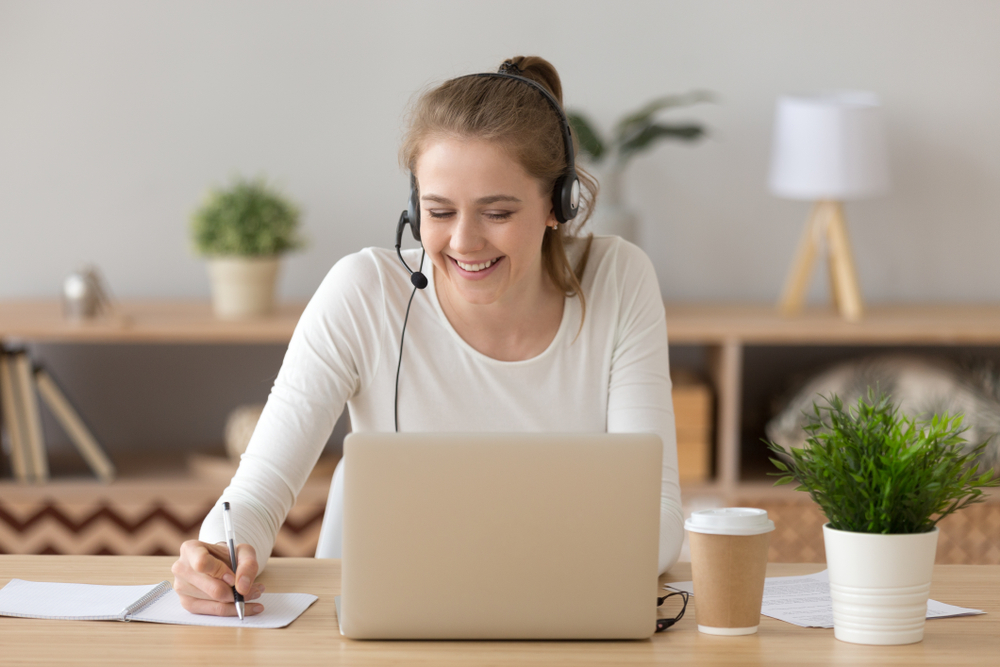 Smiling woman wear headset write notes watch webinar study work on laptop, young student in headphones learning computer course listening lecture training interpreter online teacher translating class
